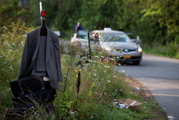 A man's suit hangs off a street marker as a cab with asylum seekers pulls up at the US-Canada border in Champlain, New York