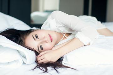 Beautiful girl wearing a white dress, sleeping in the bedroom.
