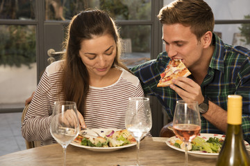 Couple eating pizza and salad