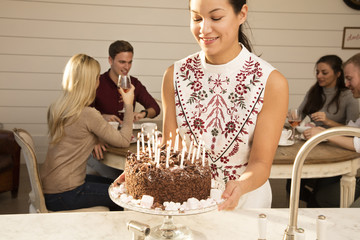 Woman arranging cake on cake stand, friends celebrating in background