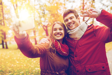 couple taking selfie by smartphone in autumn park