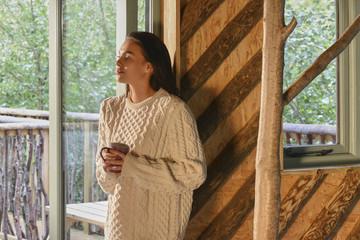 Young woman drinking coffee beside window.