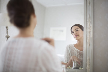Mid adult woman looking at herself in mirror.