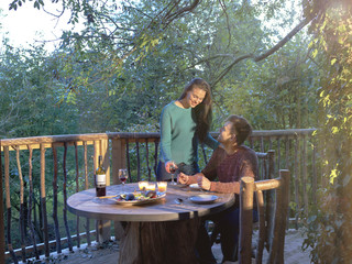 Young couple drinking wine together on log cabin balcony.
