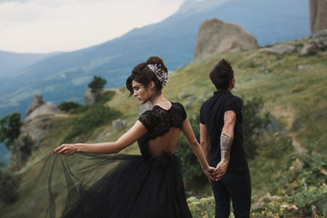 Woman and man in black clothes outdoors. Black wedding dress.