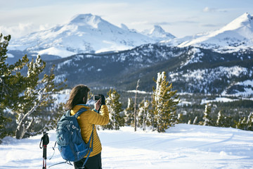 Rear view of female hiker photographing snowcapped mountains