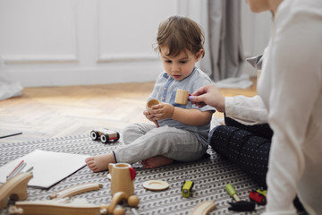 Midsection of mother giving toy teacup to baby boy while sitting on rug at home