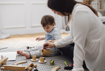 Baby boy looking at mother pouring tea in toy teacup at home