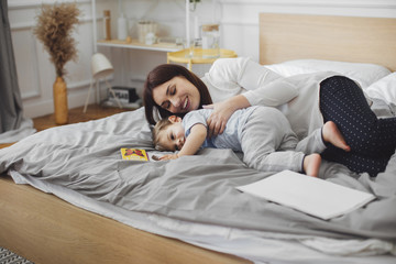 Happy mother lying with baby boy in bed at home