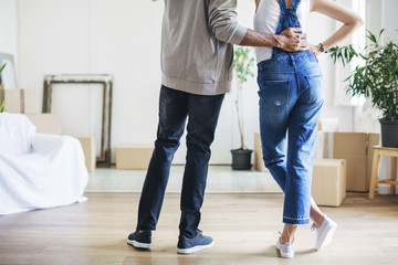 Low section of couple standing in new house