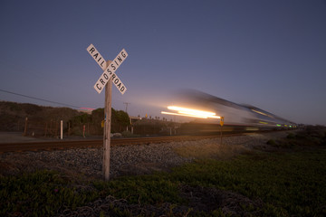 Railroad crossing sign and passing train in California