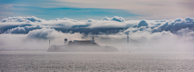 Alcatraz and the Oakland Bay Bridge through the clouds and fog.
