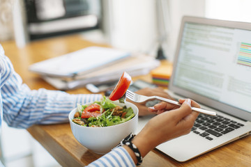 Cropped image of woman holding fork with tomato slice by laptop computer at wooden table