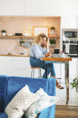 Full length of woman using smart phone while sitting at table in kitchen