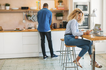 Woman using smart phone while man working at kitchen counter