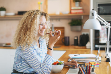 Happy young woman talking through smart phone while sitting at home office