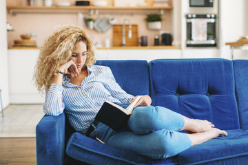Full length of woman reading diary while reclining on sofa at home