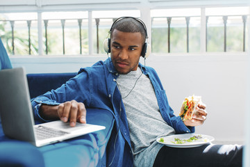Man using laptop computer while holding sandwich on sofa at home