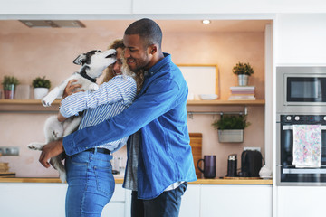 Affectionate multi-ethnic couple playing with Siberian Husky at home