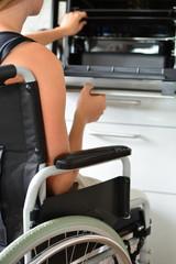 Junge Frau im Rollstuhl führt ihren Haushalt