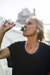 Woman drinking water while listening music