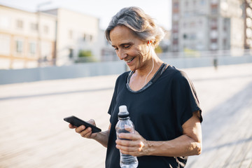 Happy woman looking at smart phone while holding water bottle