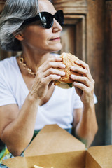 Woman in sunglasses looking away while holding burger
