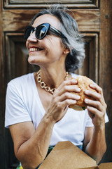 Happy woman looking away while holding burger against door
