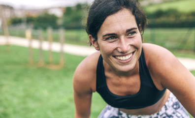 Happy woman bending while exercising at park