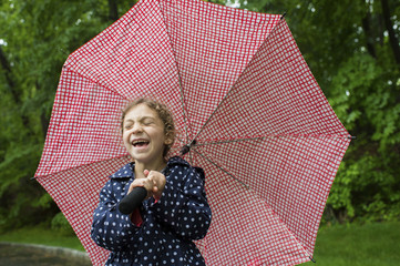 Girl laughing while holding umbrella at park