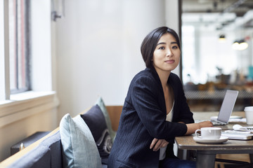 Portrait of confident businesswoman sitting at table in office
