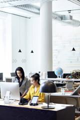 Businesswomen working on desktop computer in creative office