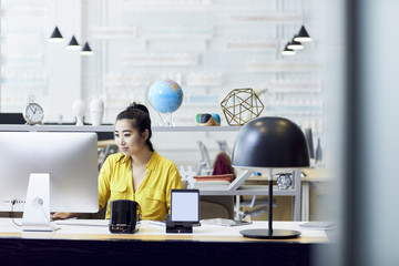 Businesswoman working on desktop computer while sitting at desk in creative office