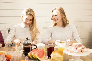 Young women eating breakfast together