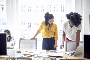 Businesswomen pointing towards document while standing against window with female colleague sitting in background