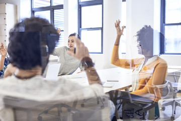 Business people voting during meeting while sitting at conference table seen through window