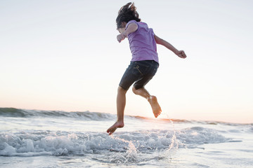 Low angle view of girl jumping on waves at beach against clear sky during sunset