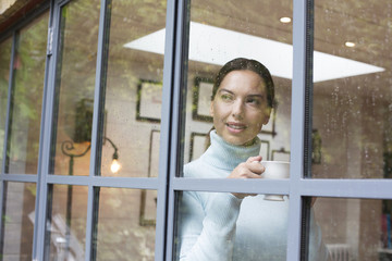 Mid adult woman drinking coffee at window.