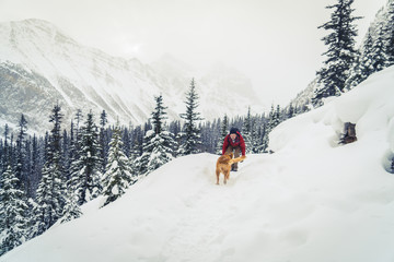 Hiker with Golden Retriever playing on snow covered field at forest
