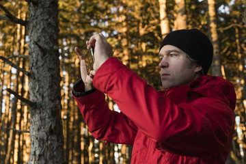 Hiker photographing through mobile phone in forest during autumn