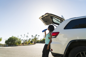 Side view of woman drinking water while leaning against car