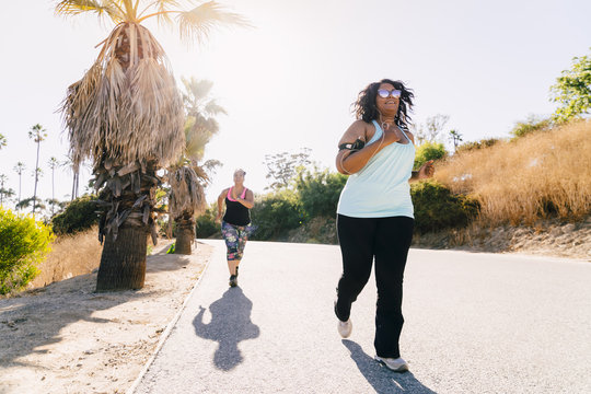 Female friends jogging on street against clear sky during sunny day