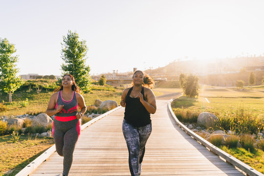 Female friends jogging on boardwalk at park