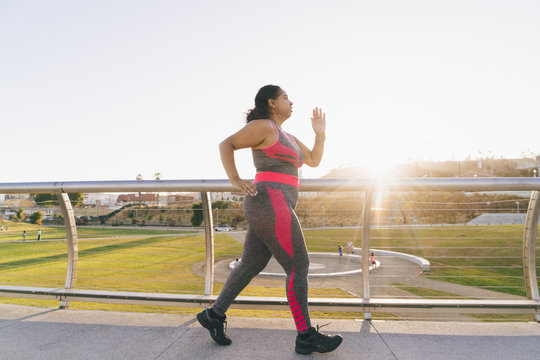 Side view of woman jogging on elevated walkway against clear sky