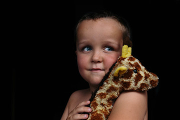 Close up of boy holding toy against black background