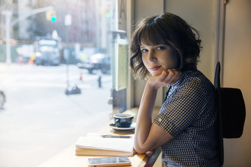 Portrait of confident woman sitting in cafe