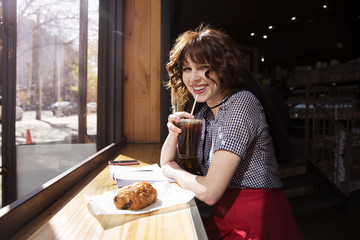 Portrait of happy woman drinking cola at cafe