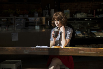 Woman looking away while drinking cola in cafe