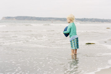 Side view of boy holding American football while standing on shore at beach