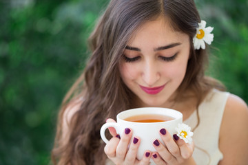 A beautiful young smiling woman with long curly hair in white top and a flower in hair holding a white cup of tea in hands, enjoying tea and looking down at the cup, green trees in the background
